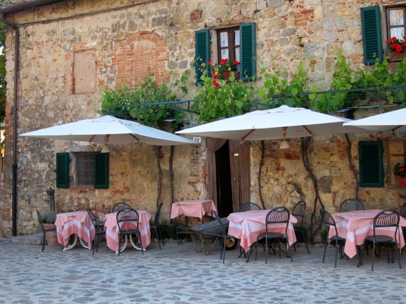 Midst medieval buildings. Pink tableclothsbeckon.